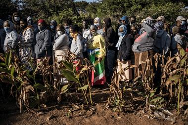 El 20 de mayo de 2020, los residentes hacen una fila para recibir cestas, máscaras, jabón y desinfectante en el asentamiento informal de Iterileng cerca de Laudium, Pretoria