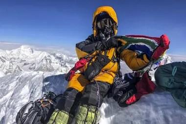 Escalador sudafricano Saray Khumalo posando en la cima del Monte Everest después de su cima