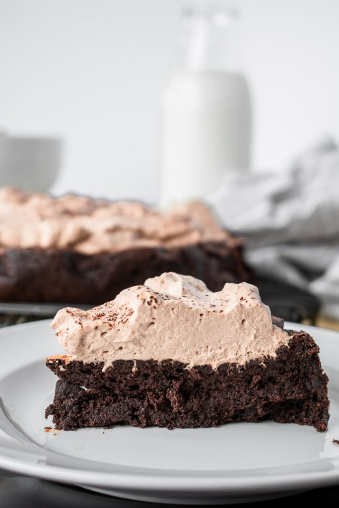 Slice of flourless chocolate cake with a thick layer of espresso whipped cream on top