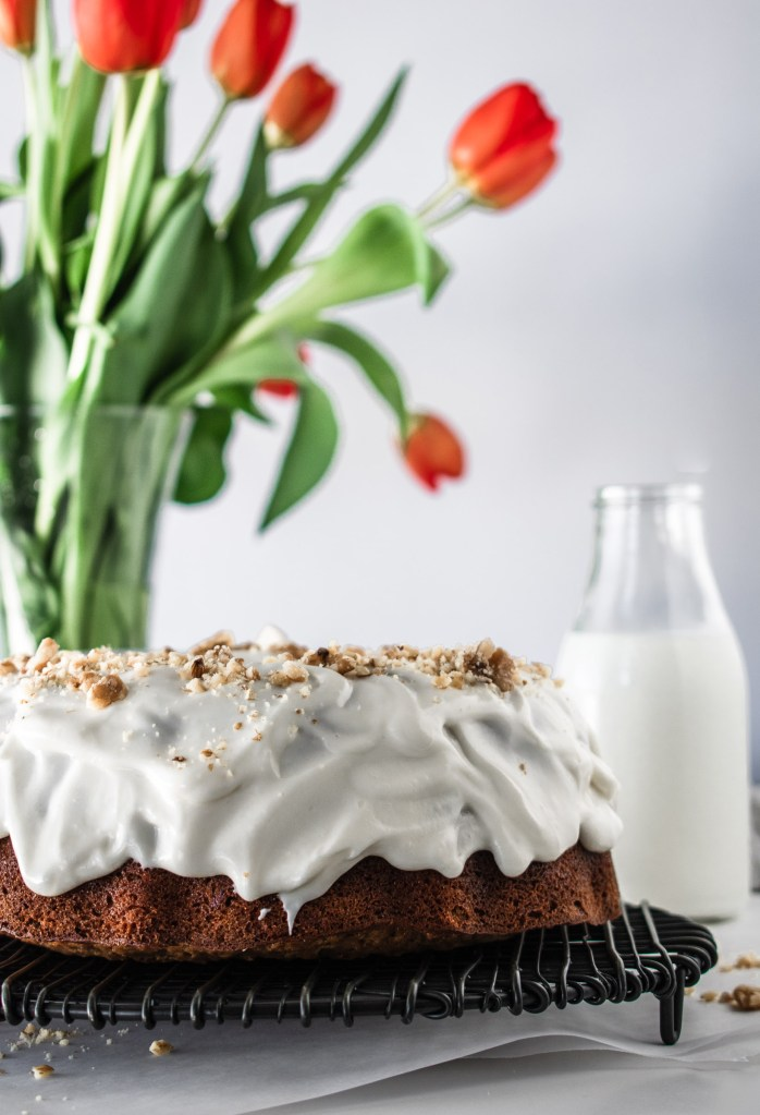 Hummingbird bundt cake on a wire rack with tulips in the background