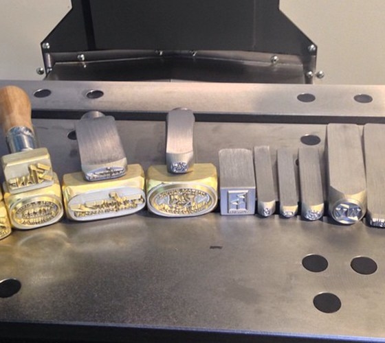 Inside Buckeye Engraving shows 15 different steel hand stamps and brass branding irons of different sizes with equipment in background