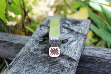 custom steel stamp for stamping jewelry crafted by Buckeye Engraving shows detailed butterfly image stamped on piece of copper jewelry