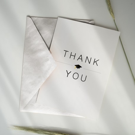 Classic thank you card tucked inside of an envelope on a table