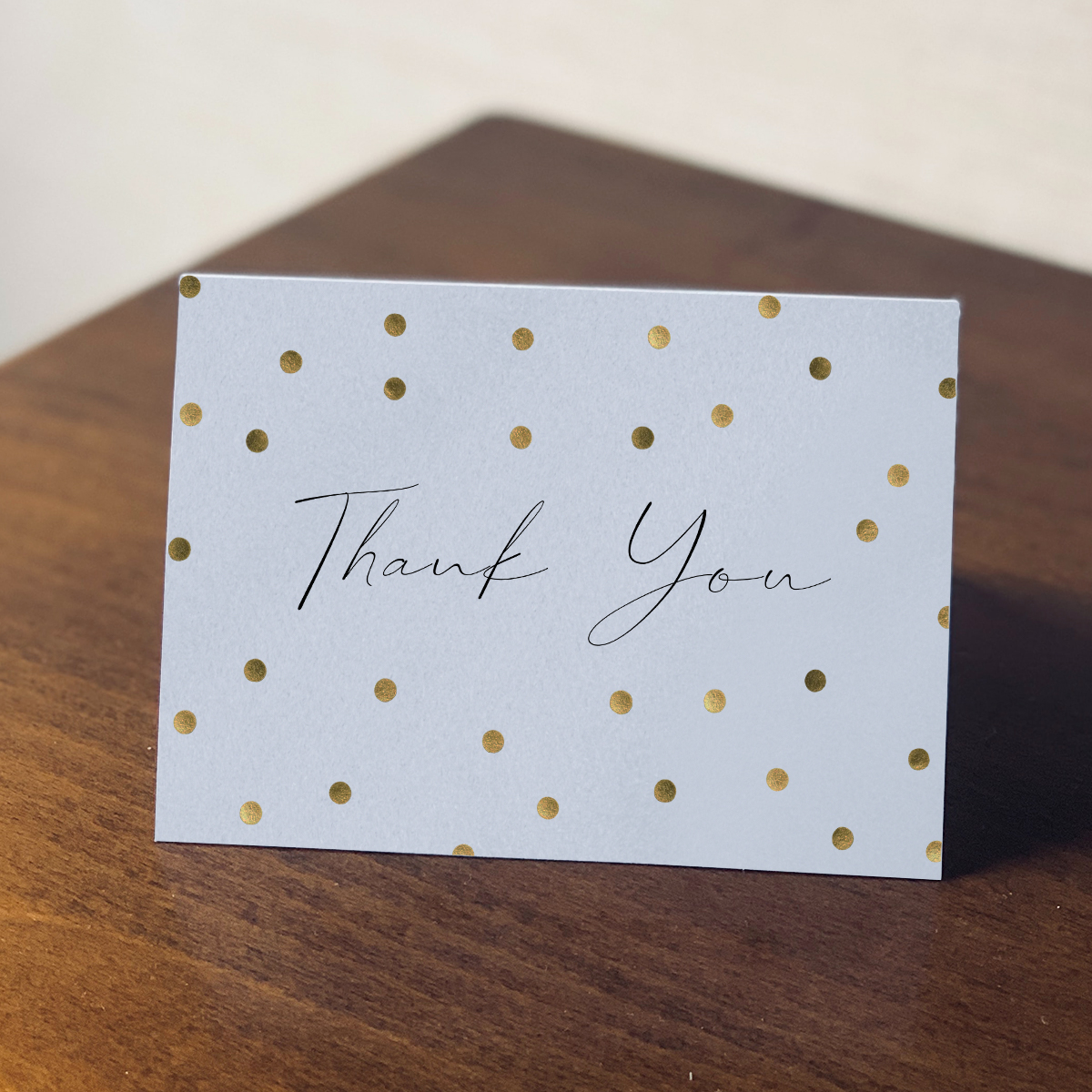 "Thank you card with script ""Thank you"" and confetti dots sitting on a table"