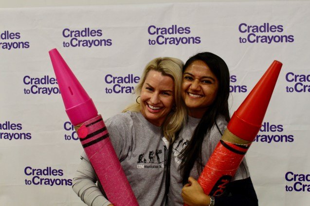 COM PR graduate candidates Sarah Dasher and Riti Shah pose with life-size crayons at the Cradle to Crayons' Giving Factory. Photo credit: Xia Xue.