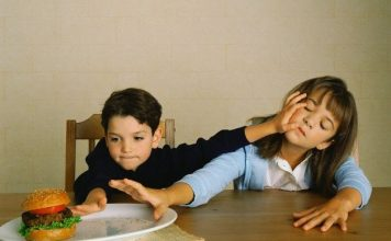 Siblings Fighting over Hamburger --- Image by © Anthony Redpath/Corbis