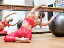 Young woman doing pilates mermaid exercises