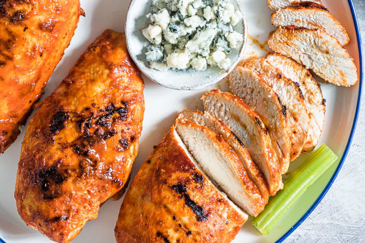 close up of grilled buffalo chicken on a plate some sliced with garnishes