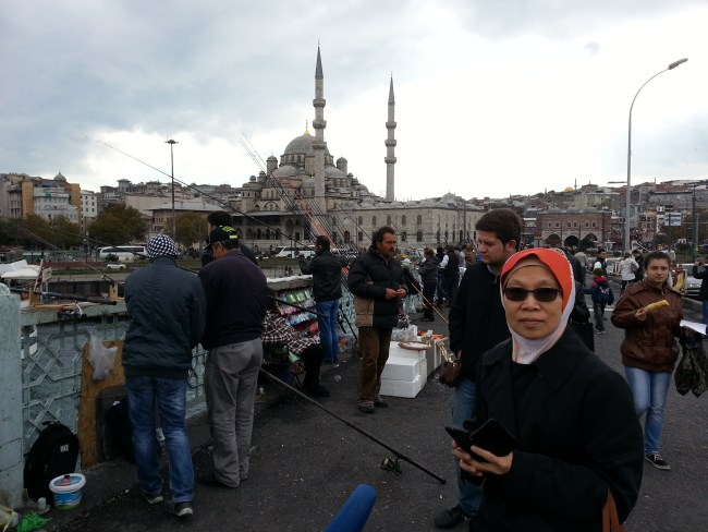 FISHING ON THE BRIDGE & NEW MOSQUE IN THE BACKGROUND