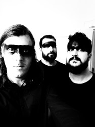 New Ghost -black and white photo with three band members with black stripes across their eyes