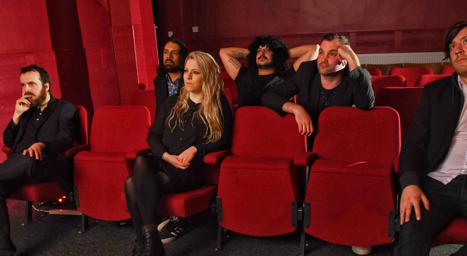 New Ghost - band members sitting in cinema