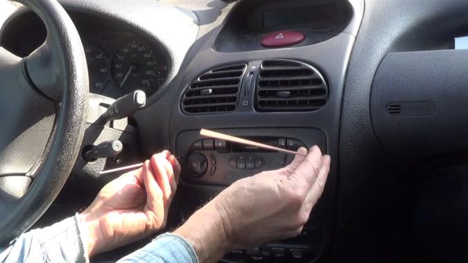 Insérer les 2 tiges dans les 2 trous de l'autoradio pour le déverrouiller