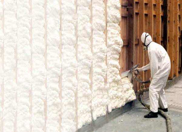 Trained applicator applying spray polyurethane foam insulation in wall cavities.