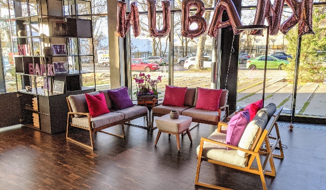 Nubank's office at Mitte neighborhood in Berlin: ballons with the letters of Nubank hanging in the living with couches and the streets seen outside.