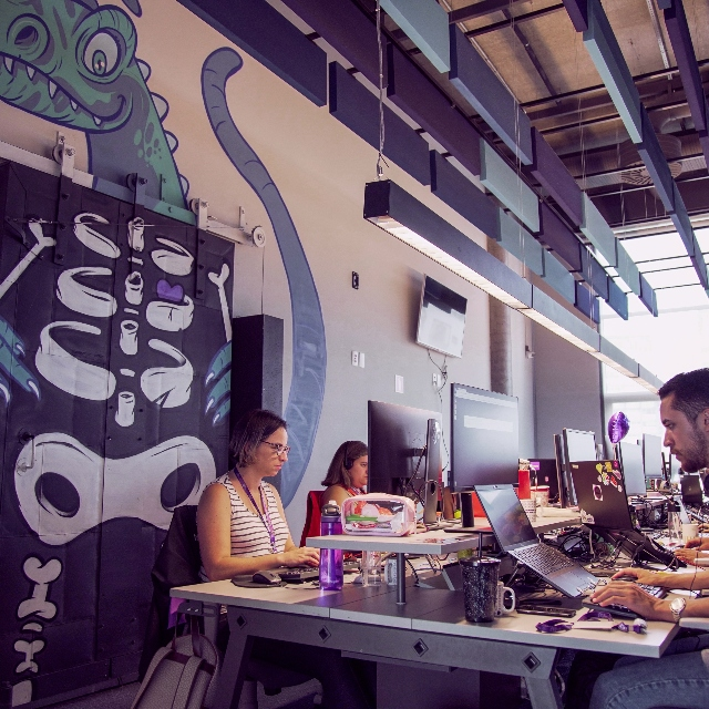 Why We Killed Our End-to-End Test Suite. Nubankers working at the office of Nubank in Sao Paulo with a dinosaur painted on the wall behind.