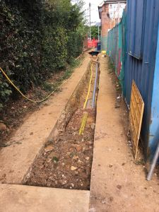 Utility service trench backfilled with marker tape