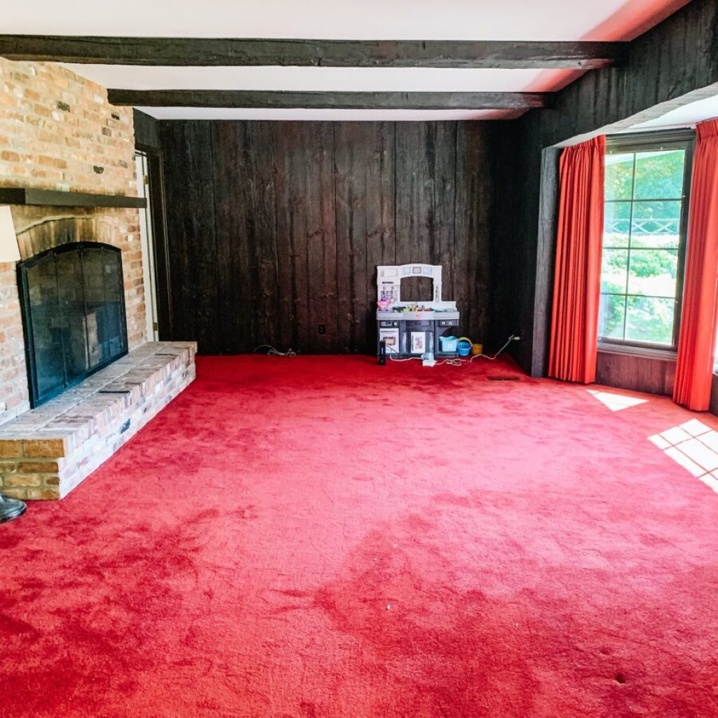 The back den, family room with red carpet and faux wood walls.