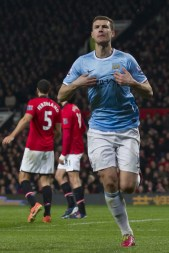 Manchester City's Edin Dzeko celebrates after scoring his second goal against Manchester United during their English Premier League soccer match at Old Trafford Stadium, Manchester, England, Tuesday, March 25, 2014. (AP Photo/Jon Super)