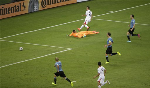 Costa Rica's Marco Urena, top, scores his side's 3rd goal during the group D World Cup soccer match between Uruguay and Costa Rica at the Arena Castelao in Fortaleza, Brazil, Saturday, June 14, 2014. (AP Photo/Sergei Grits)