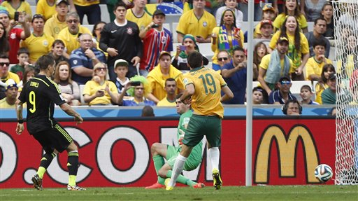 Spain's Fernando Torres, left, scores his side's second goal during the group B World Cup soccer match between Australia and Spain at the Arena da Baixada in Curitiba, Brazil, Monday, June 23, 2014. (AP Photo/Jon Super)