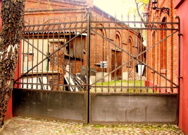 Stara brama obok budynku straży ogniowej prowadzi na podwórko