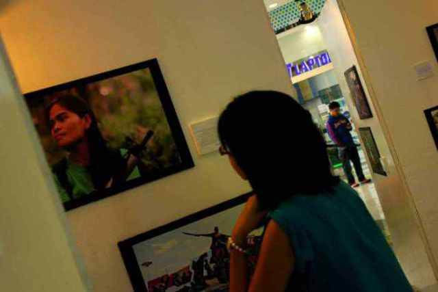 A young woman looks at the photograph of a woman guerrilla who continues Andres Bonifacio's  unfinished revolution. (Photo by Southern Tagalog Exposure)