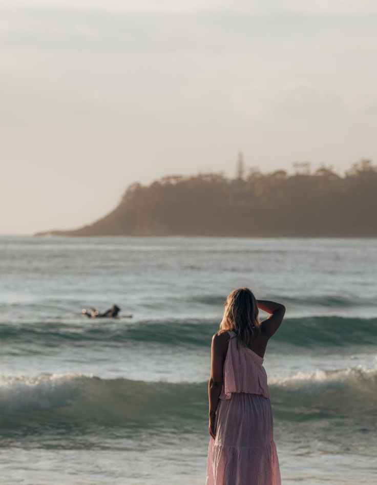 unrecognizable female admiring waving ocean view on coast