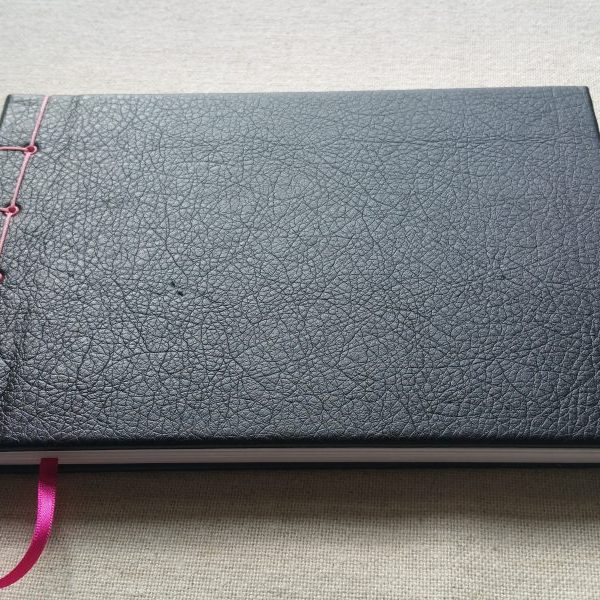 A black leatherette notebook with pink detailing