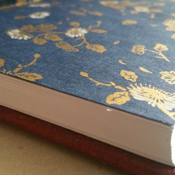 A red leather journal is opened to reveal navy blue endpapers and white pages.