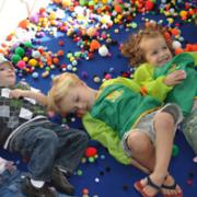 Children on floor covered in craft supplies