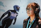 Marine biologist Anna Bakker stands in front of main character Mirai as she plays through a demo of Beyond Blue, an open-world oceanic exploration game from E-Line Media at the Boston Exhibition and Convention Center in Boston, MA.