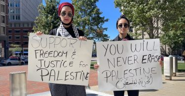 Palestinian protestors pose with posters