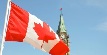 A photo of the Canadian flag flying in the wind in Ottawa with a clock tower behind it.