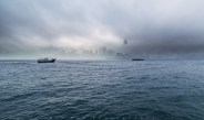 Foggy morning on the Kowloon side of Victoria Harbour. Sunlights breaking through the intense fog showing some lights and silhouette shading in some of the building across the ocean on Hong Kong island