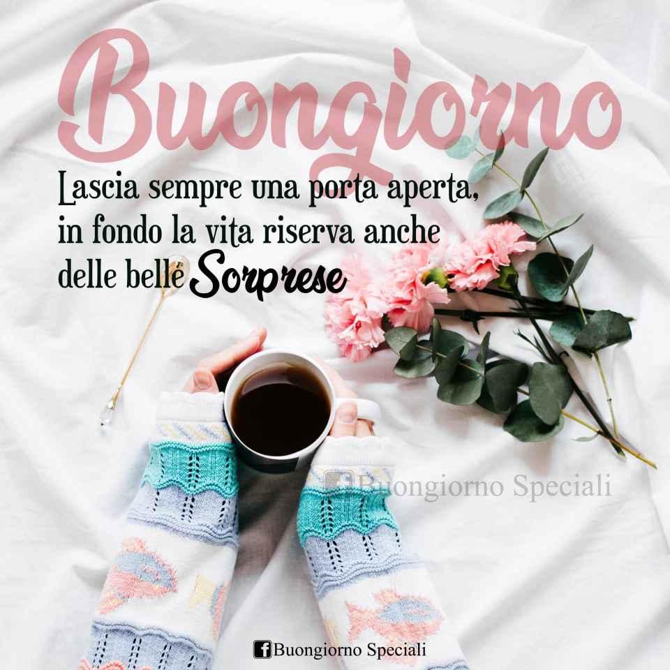 Braccia che stringono una tazza di caffè e fiori rosa appoggiati accanto. Scritta: Lascia sempre una porta aperta, in fondo la vita riserva anche delle belle sorprese. Buongiorno
