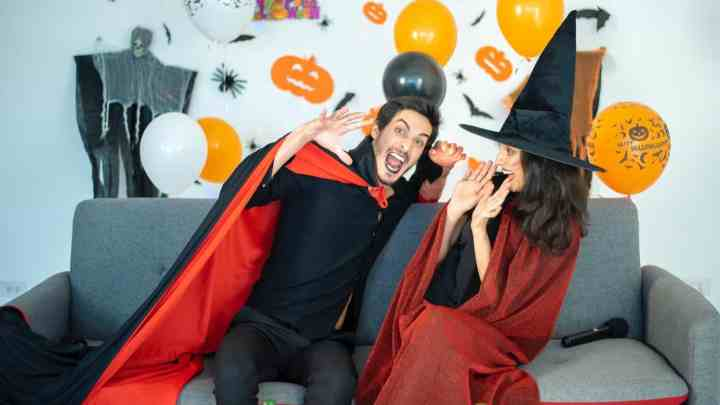 man and woman sitting while wearing halloween costumes