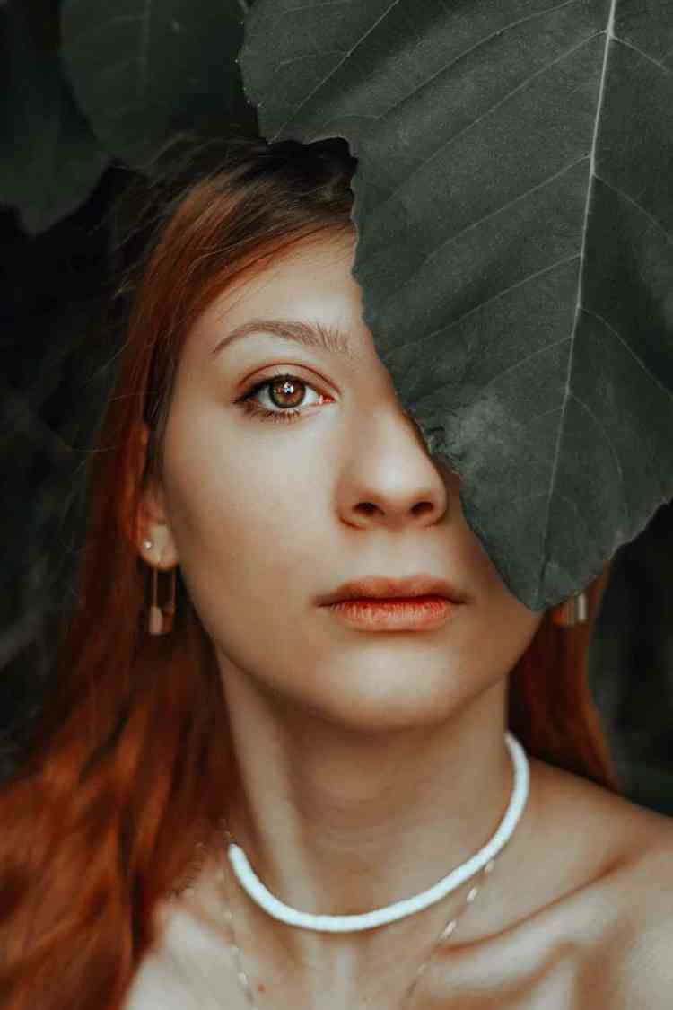 beautiful woman with leaf on face