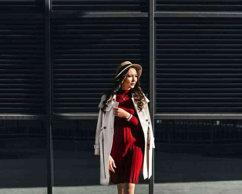 stylish woman crossing road against modern building