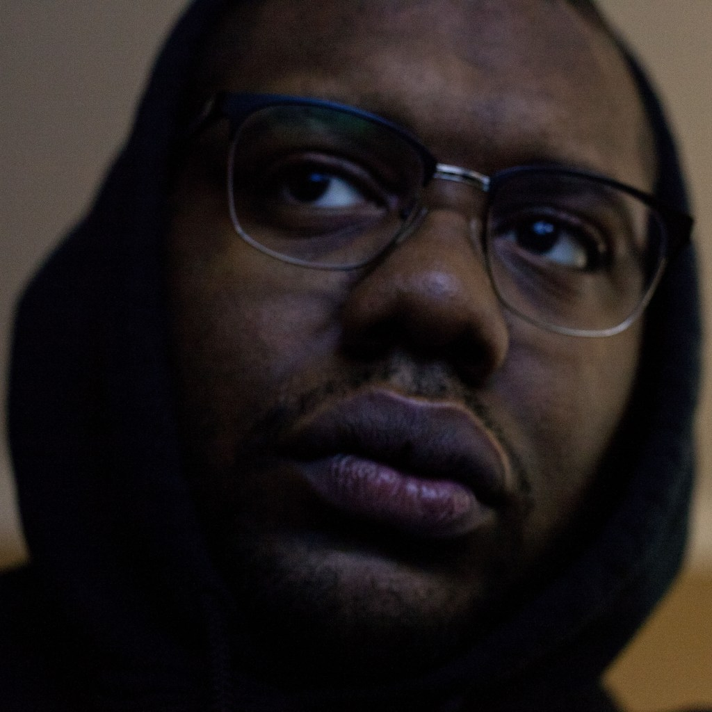 A close-up picture of David Collins face. David is a young Black man wearing glasses and a hoodie, looking pensively off to the side.