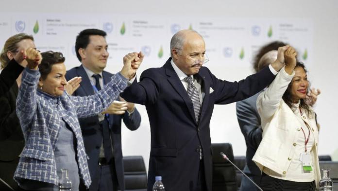 Cet accord sur le climat est aussi une victoire pour la diplomatie française ; Laurent Fabius (au milieu) célébrant la signature de l'accord avec d'autres artisans