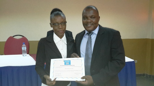Une participante recevant son attestation des mains du président de Think Thank, Paul Oumarou Koalaga