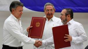 shake hands during a signing ceremony of a cease-fire and rebel disarmament deal, in Havana, Cuba. (AP Photo)
