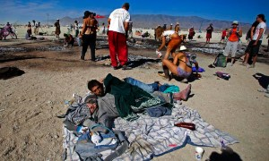 "Xander Shepherd and Cole Purdy, grey sweater, sleep at the base where The Man was burned during the Burning Man 2011 ""Rites of Passage"" arts and music festival in the Black Rock desert of Nevada"