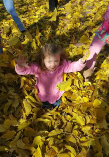 kid playing in leaves