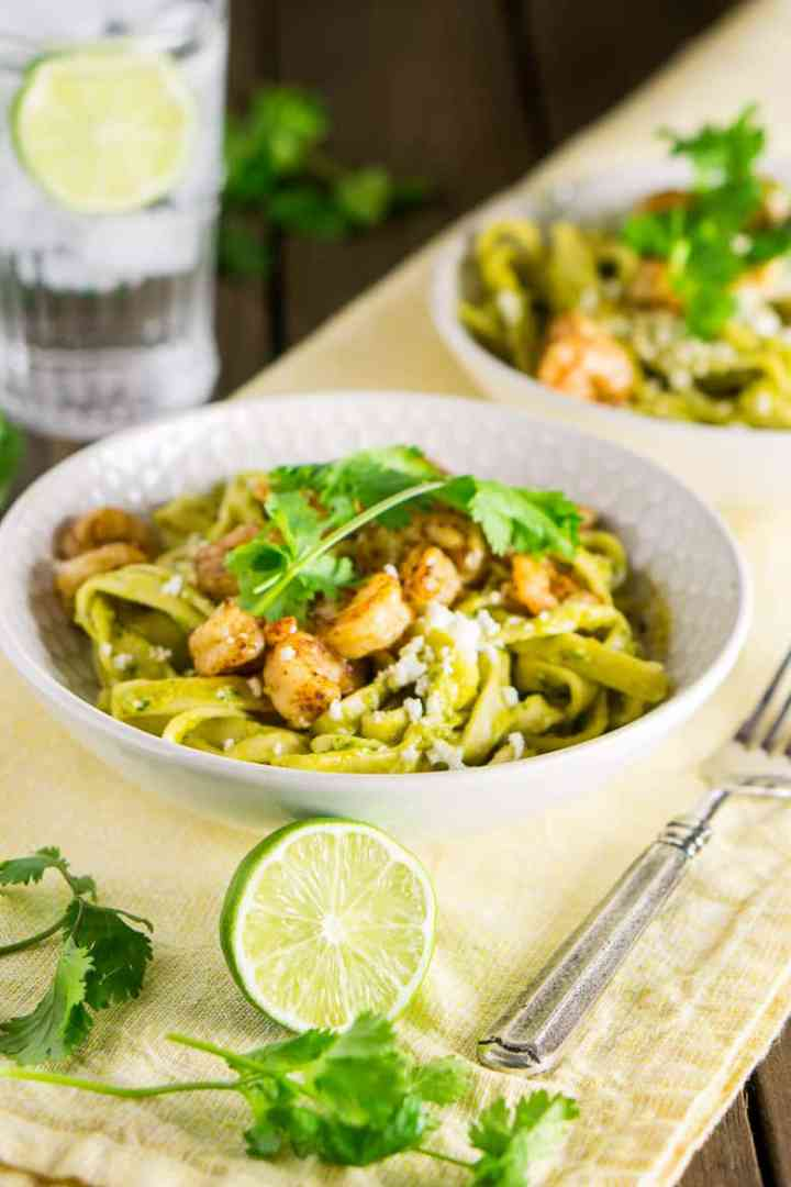 A bowl of Tex-Mex avocado pasta on a yellow napkin with lime and cilantro on the side.