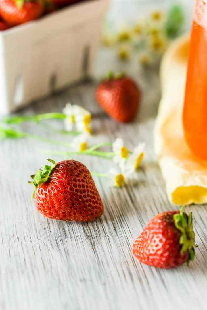 A close-up of a fresh strawberry with a roasted strawberry Aperol spritz to the side.