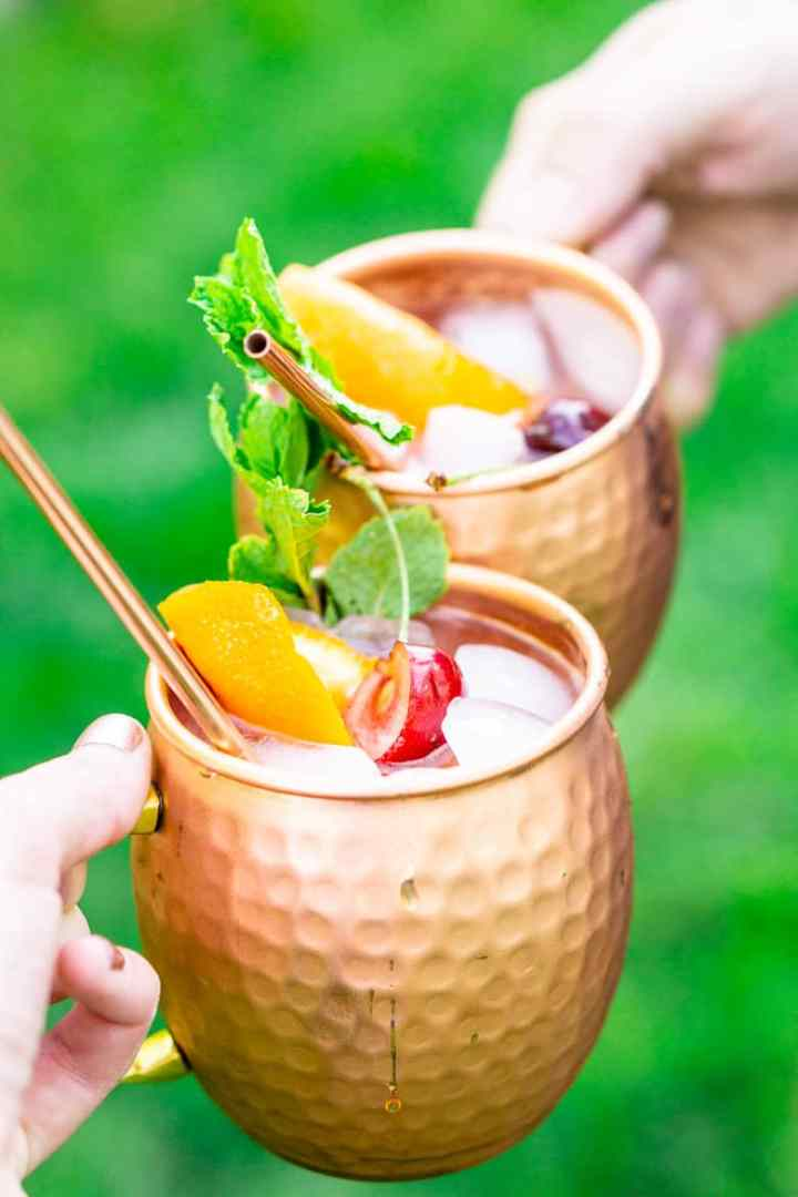 Two people clinking their cherry orange Kentucky mule outside with grass in the background.