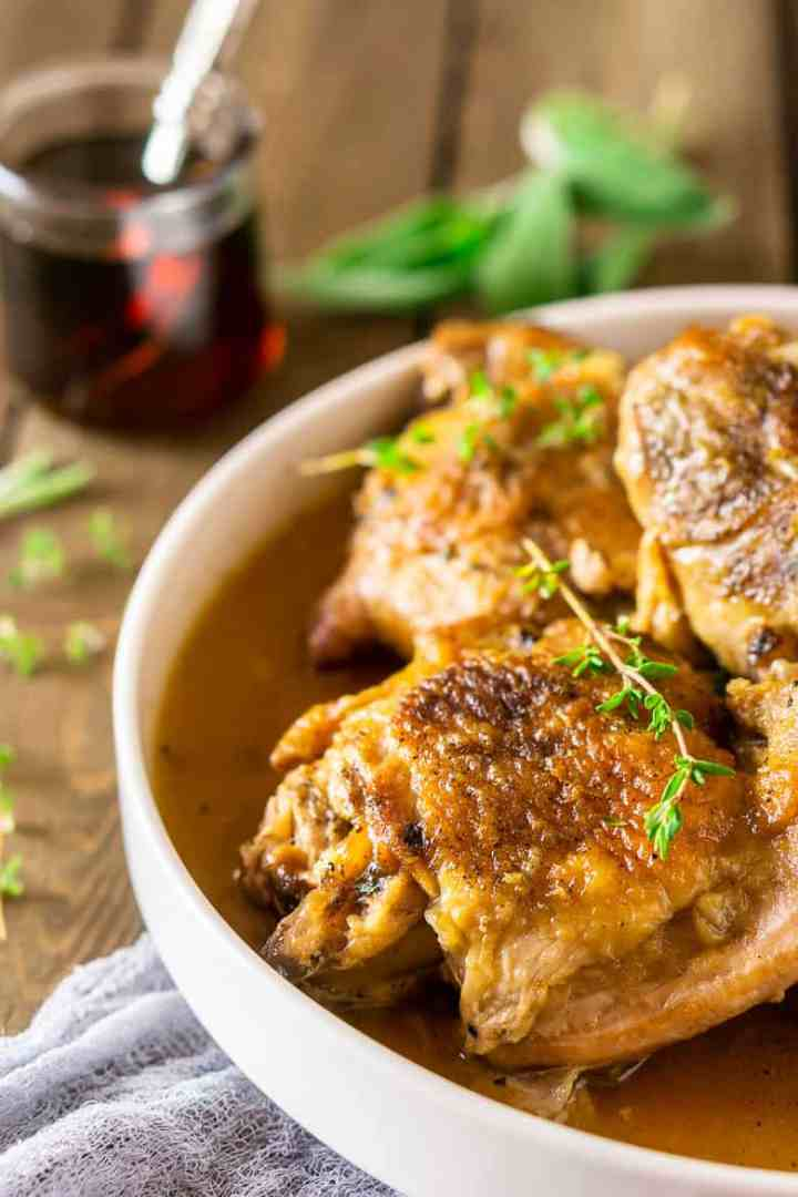 Maple-braised turkey legs and thighs on a white platter surrounded by fresh thyme.