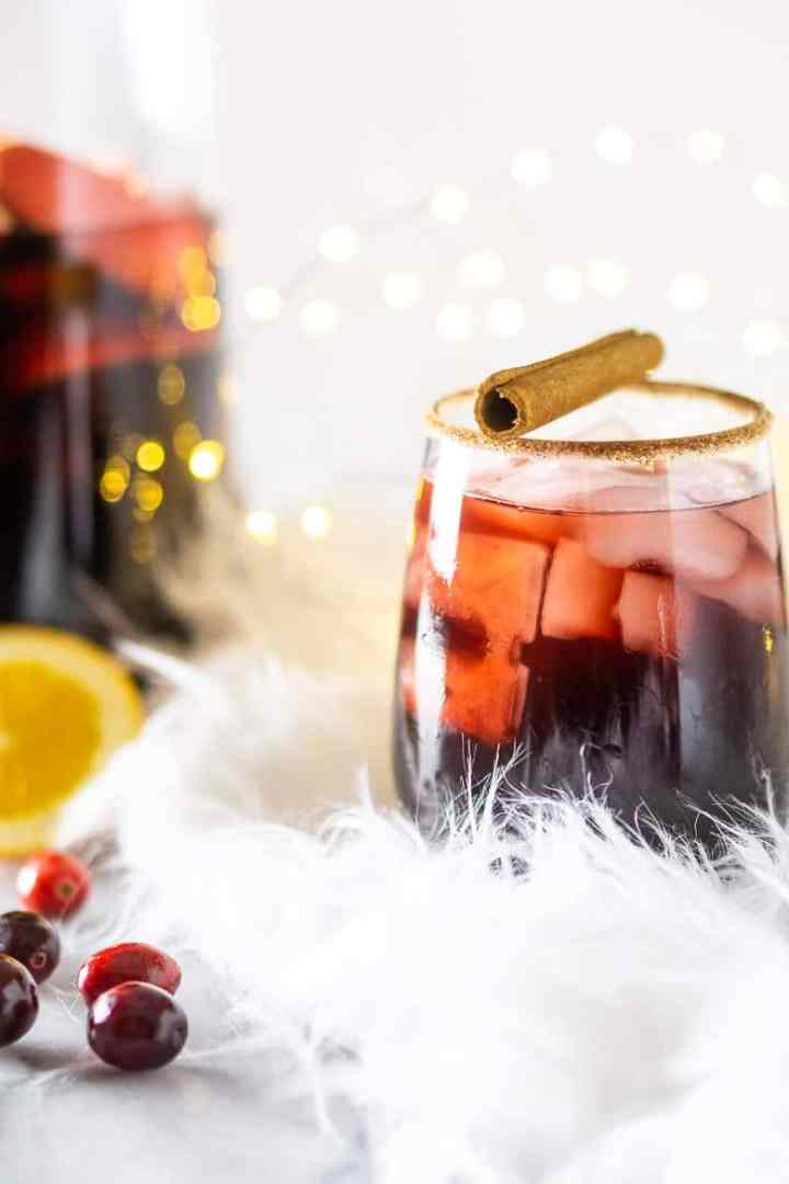 A front view of holiday sangria with cinnamon stick on top and the pitcher in the background.