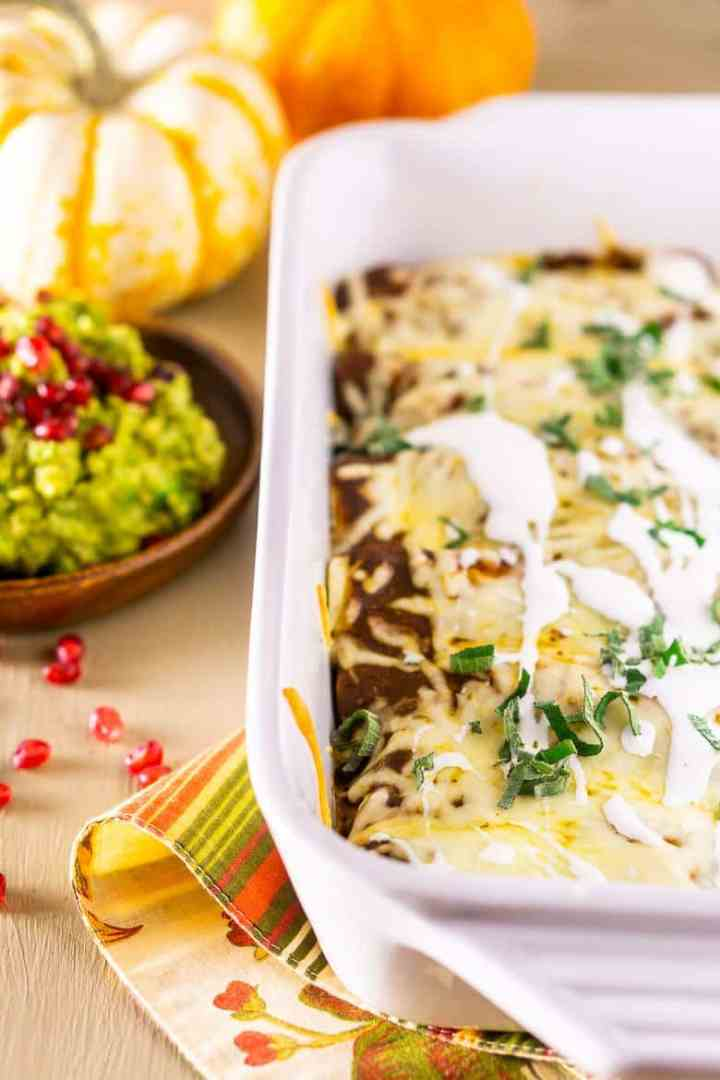 A pan of Thanksgiving enchiladas with pomegranate guacamole and pumpkins as decor